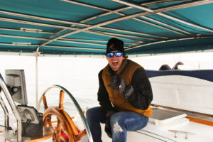 Kyle Sailing Seas LYFE Vessel. large wooden wheel,blue overhang, a he wears a yellow jacket and black beanie